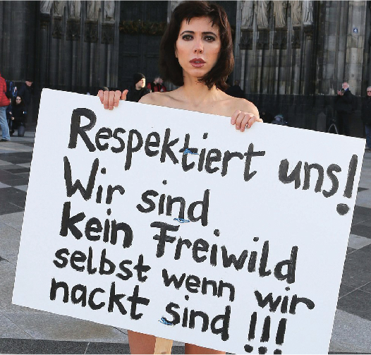 'Respect Us! We are not fair game even when naked!!!' read a simply painted protest sign created by Milo Moire on Friday. The Swiss artist wore the sign and little else during her performance in front of the Cologne Cathedral on Friday, which was a nude protest against sexual assault in the city.